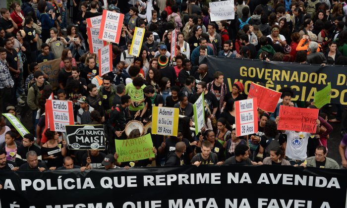 Demonstrators block Brasil Avenue, the main access to Rio de Janeiro, in front of the Favelas de Mare Complex, during a protest against violence by the militarized police, on July 2, 2013. (Vanderlei Almeida/AFP/Getty Images)