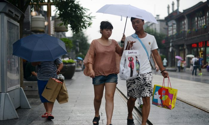 A couple carry shopping bags along a street in Beijing, on July 9, 2013. As Chinese exports slow, domestic consumption in the world's most populated country is failing to pick up the slack. (Wang Zhao/AFP/Getty Images)
