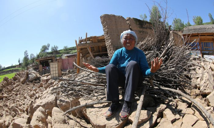 A resident cries on her collapsed house in Hetuo Township in Dingxi, northwest China's Gansu province on July 22, 2013. Double tremors killed 73 people and injured almost 600, officials said. (STR/AFP/Getty Images)
