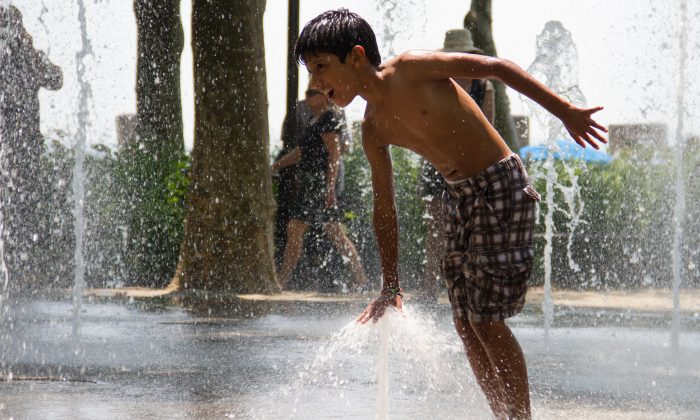 Children beat the summer heat by cooling off in a water play area in New York City's Battery Park on June 26, 2012. (Benjamin Chasteen/The Epoch Times)