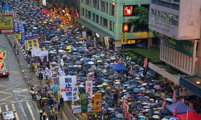 Thousands braved heavy rain to attend the annual July 1 pro-democracy march in Hong Kong. Hong Kong residents called for universal suffrage and for the chief executive Leung Chun-ying to step down from office. (Poon Zoi-syu/Epoch Times)