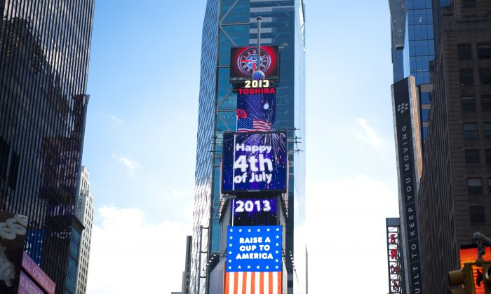 A billboard in Times Square displays Happy July 4th with fireworks messages. (Samira Bouaou/Epoch Times)