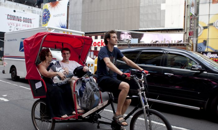 A couple enjoys a breezy ride in a New York City pedicab on July 10. (Samira Bouaou/Epoch Times)