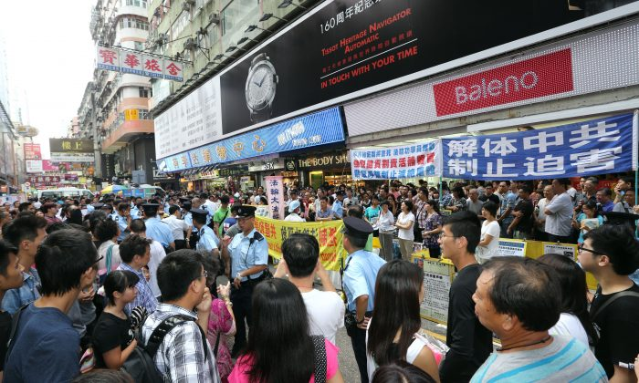 A crowd gathers in front of a Falun Gong information site in Mong Kok District. Members of the Hong Kong Youth Care Association were harassing the practitioners on July 14, prompting bystanders to confront the police for their failure to intervene. (Poon Zoi-syu/Epoch Times)