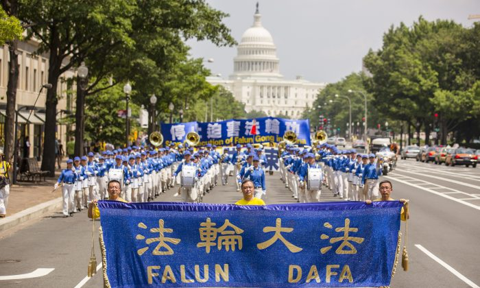 Three Falun Dafa practitioners lead the Divine Land Marching Band with a blue and gold banner. Adherents of the practice march down from 3rd & 4th Street to the Monument in Washington, D.C. on July 18. (Edward Dai/Epoch Times)