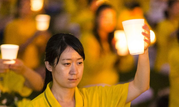 A Falun Gong practitioner holds a candle aloft, at a candlelight vigil on the National Mall in Washington, D.C. on July 18, 2013. (Edward Dai/Epoch Times)