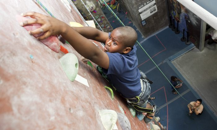 Moses Kamara climbs a wall at the Brooklyn Boulders on July 22. (Samira Bouaou/Epoch Times)