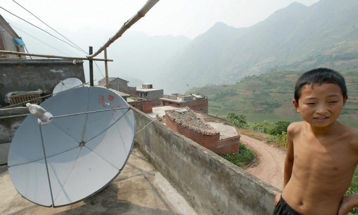 In this file photo, a young Chinese boy stands next to a satellite dish on the roof of his home. Thirteen Falun Gong practitioners are on trial in Dalian for installing satellite dishes used to receive the independent, New York-based NTD Television. (Goh Chai Hin/AFP/Getty Images)