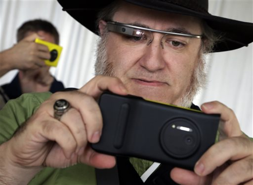 Journalist wearing Google Glass, tests a Nokia Lumia 1020 at its introduction,  in New York,  Thursday, July 11, 2013. (AP Photo/Richard Drew)