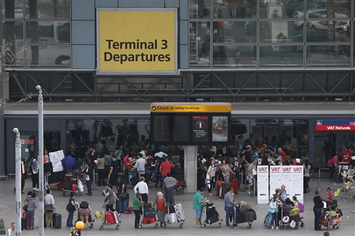 Passengers queue outside Terminal 3 at Heathrow Airport in London, Friday, July 12, 2013.  (AP Photo/Sang Tan)