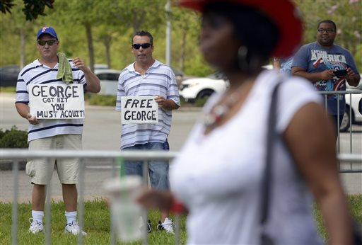 Patrick Woodburn, left, and William Memola hold signs supporting George Zimmerman in front of the Seminole County Courthouse, Saturday, July 13, 2013, in Sanford, Fla. (AP/Phelan M. Ebenhack)