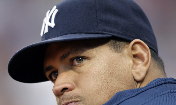 In this Aug. 22, 2009, file photo, New York Yankees' Alex Rodriguez watches from the dugout in the eighth inning of a baseball game against the Boston Red Sox at Fenway Park in Boston.  Baseball is threatening to kick Rodriguez out of the game for life unless the Yankees star agrees not to fight a lengthy suspension for his role in the sport's latest drug scandal, according to a person familiar with the discussions. (AP Photo/Elise Amendola, File)