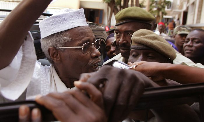 FILE -In this Friday, Nov. 25, 2005, file photo,  Former Chad dictator Hissene Habre, left,  seen as he leaves the court in Dakar, Senegal. A French lawyer for ex-Chadian dictator Hissene Habre confirms he has been charged with war crimes, crimes against humanity and torture by a special court set up in Senegal to try him. Lawyer Francois Serres told The Associated Press the judges have ordered Habre detained. He has been in police custody since Sunday June 30, 2013, when he was taken away from his villa in Senegal's capital. (AP Photo/Schalk van Zuydam, File)
