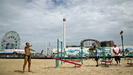 The Astrotower, center, at the Coney Island amusement park looms in the background as visitors exercise on a nearby beach on Wednesday, July 3, 2013. Crews working to dismantle the Astrotower have reduced the 275-foot tower to 145 feet tall, and demolition crews using huge cranes planned to take down another 27-foot section Friday, said Chris Miller, a spokesman for the city's Office of Emergency Management. (AP Photo/Bebeto Matthews)