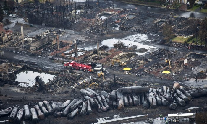 Workers comb through debris on July 9 after a run away oil train derailed July 6, 2013 causing explosions, fire and destroying parts of Lac-Megantic, Quebec. (AP Photo/The Canadian Press, Paul Chiasson)