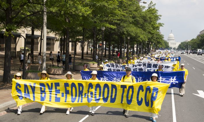 """Falun Dafa practitioners carry a banner """"Say Goodbye to the CCP"""" in a parade in Washington, D.C. on July 18, 2013. As of July 16, over 142 million Chinese have renounced any association with the Chinese Communist Party and its affiliate organizations. (Edward Dai/Epoch Times)"""