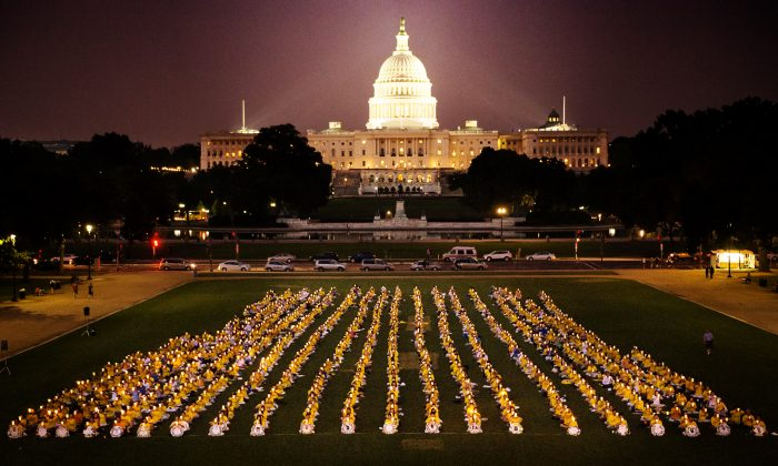 """To commemorate the anniversary of the beginning of the persecution of Falun Gong, practitioners hold a candlelight vigil on the National Mall on July 18, 2013 in Washington, D.C. The two Chinese characters """"zheng fa"""" illuminated at the front of the vigil may be translated as """"healing the universe."""" (Edward Dai/Epoch Times)"""