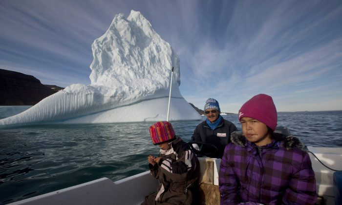 In this July 21, 2011 photo, Inuit hunter Nukappi Brandt steers his small boat as he and his daughter Aaneeraq, 9, scan the water for seals, accompanied by his other daughter Luusi, 8, outside Qeqertarsuaq, Disko Island, Greenland. The country, impacted by global warming causing ice sheets to melt, is the largest island in the world. (AP Photo/Brennan Linsley)