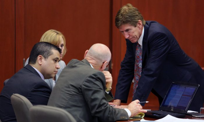 George Zimmerman, left, confers with his defense counsel, Mark O'Mara, Don West, and Lorna Truett, background. O'Mara said after the not guilty verdict that Zimmerman wouldn't have been charged in the 2012 shooting death of Trayvon Martin if he were black. (AP Photo/Orlando Sentinel, Joe Burbank, Pool)