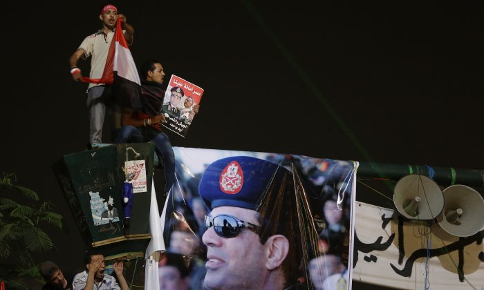 Opponents of ousted President Mohammed Morsi stand next to a poster of Egyptian Defense Minister General Abdul Fatah al-Sisi during a rally at Tahrir square in Cairo, July 19, 2013.(AP Photo/Hussein Malla)