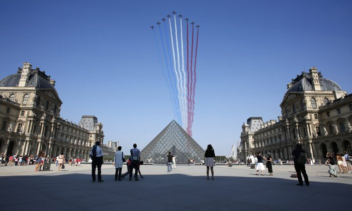 Nine alphajets from the French Air Force Patrouille de France releasing trails of red, white and blue smoke, colors of French national flag, fly over the Pyramid du Louvre during the Bastille Day parade in Paris on July 14, 2013. (Thomas Coex/AFP/Getty Images)
