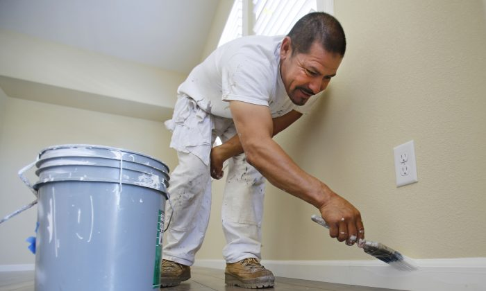 Painter Salvador Escoto paints the baseboard of a house under construction in Sacramento, Calif., Friday June 21, 2013. (AP/Rich Pedroncelli)
