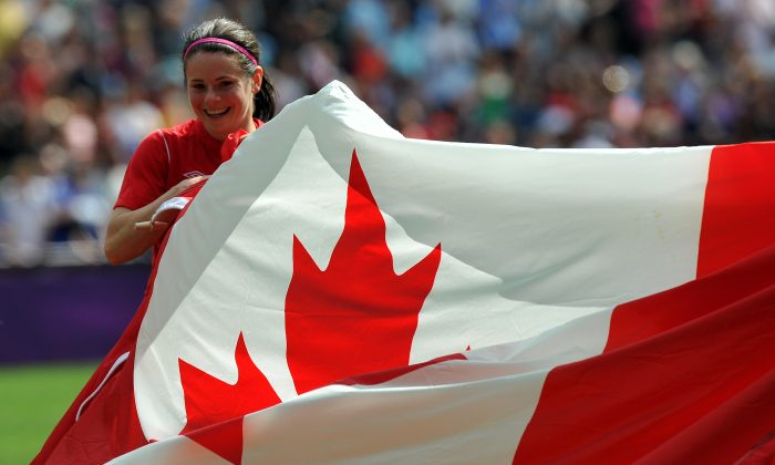 A stock photo of a Canadian flag, held by midfielder Diana Matheson at the women's football match for bronze of the London 2012 Olympic Games on Aug. 9, 2012. As Canada celebrates its birthday on July 1, many French Canadians move house instead. (Paul Ellis/AFP/GettyImages)