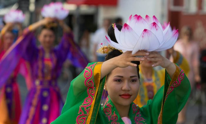 A Falun Gong practitioner carries a paper lotus flower in a parade through the streets of Copenhagen on July 20, 2013. (Matthias Kehrein/Epoch Times)
