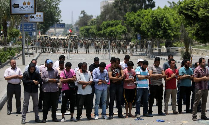 Egyptian supporters of deposed President Mohammed Morsi pray in front of barbed wire fencing that blocks the access to the headquarters of the Republican Guard in Cairo on July 8, 2013. (Mahmud Hams/AFP/Getty Images)
