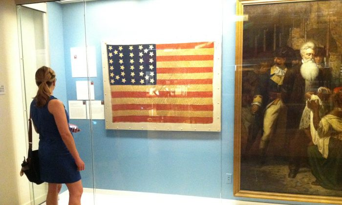 A woman stands in front on an 1861 American flag with 34 stars on it at the New York Historical Society Museum and Library in Manhattan on July 4. The museum hosted a day of educational exhibits, activities and performances throughout the day.