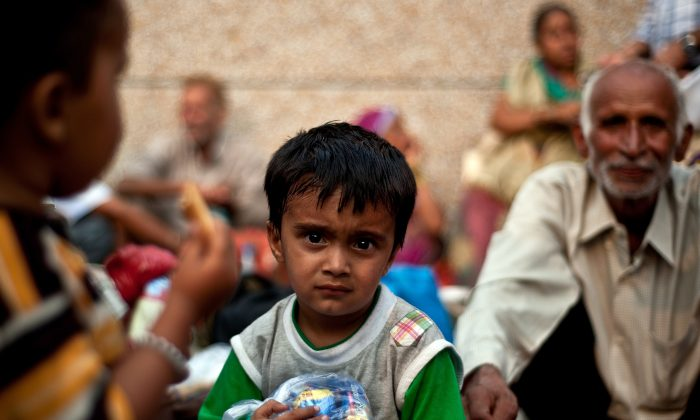 An Indian boy rescued from flood-hit areas waits with others before being sent to relief camps in Dehradun, the state capital of Uttarakhand, on June 21, 2013. (Manan Vatsyayana/AFP/Getty Images)