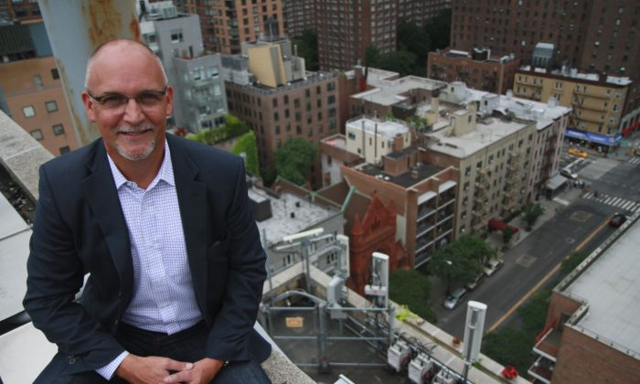 Joe Meyer, vice president of network service management at Sprint, sits on the rooftop of a Holiday Inn on W. 57th St. in Manhattan in Manhattan on July 25, 2013. At bottom right are antennas and radioheads that beam Sprint's 3G, 4G, and voice cellular service to the streets, sidewalks, and buildings below. (Ivan Pentchoukov/Epoch Times)