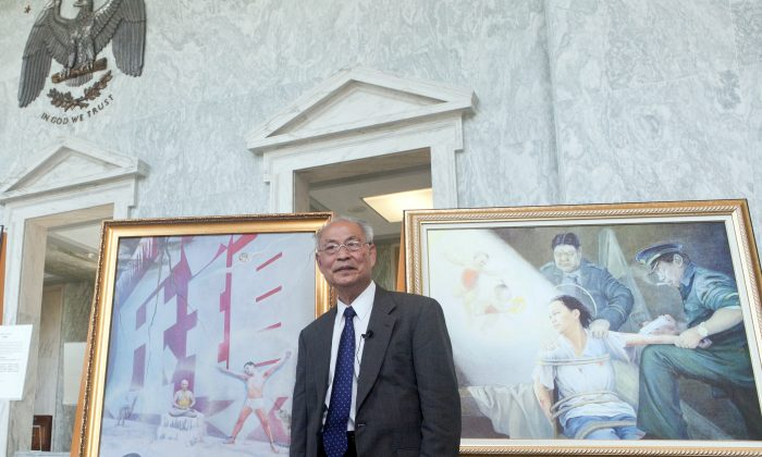 """Professor Kunlun Zhang with his painting """"Red Wall,"""" which is based on his experience as a prisoner of conscience in China. Zhang, a sculptor, believes art is the best way to communicate the beauty of his spiritual discipline Falun Gong, and the brutality of the persecution in China. (XIMING/EPOCH TIMES)"""