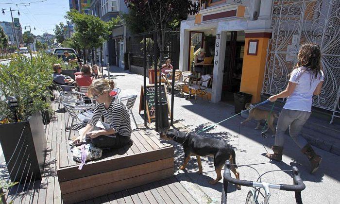People enjoy the sun at a parklet on Divisadero Street in San Francisco, June 11, 2010. (AP Photo/Eric Risberg)