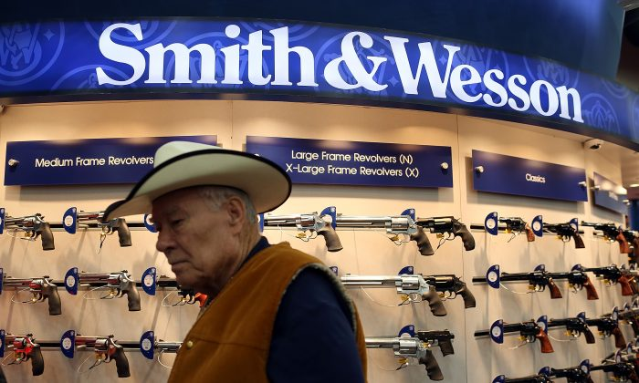 An attendee walks through the Smith and Wesson booth during the 2013 NRA Annual Meeting and Exhibits at the George R. Brown Convention Center in Houston, Texas, on May 3, 2013. New York Public Advocate Bill de Blasio announced July 22 that eight hedge funds and money managers have divested gun holdings valued at $150 million. (Justin Sullivan/Getty Images)