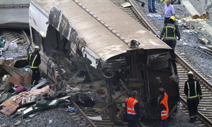 Rail personnel and firefighters inspect the derailed cars at the site of a train accident in Santiago de Compostela, Spain, on Thursday, July 25, 2013.  (AP Photo/ Lalo Villar)