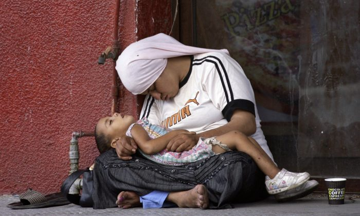 A Syrian refugee woman holds her child as they doze off on the sidewalk of a street in the southern Lebanese city of Sidon on July 18, 2013. The exodus of Syrian refugees accelerated dramatically in recent months, with over 1 million refugees arriving in the first five months of 2013 alone. More than half of registered refugees are children and three-quarters of registered refugees are living with local host families and communities in both urban and rural areas. (Mahmoud Zayyat/AFP/Getty Images)