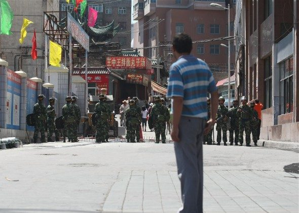 A Uyghur man looks at Chinese policemen blocking a street on July 9, 2009 in Urumqi, the capital of Xinjiang Uyghur autonomous region, China. (Guang Niu/Getty Images)