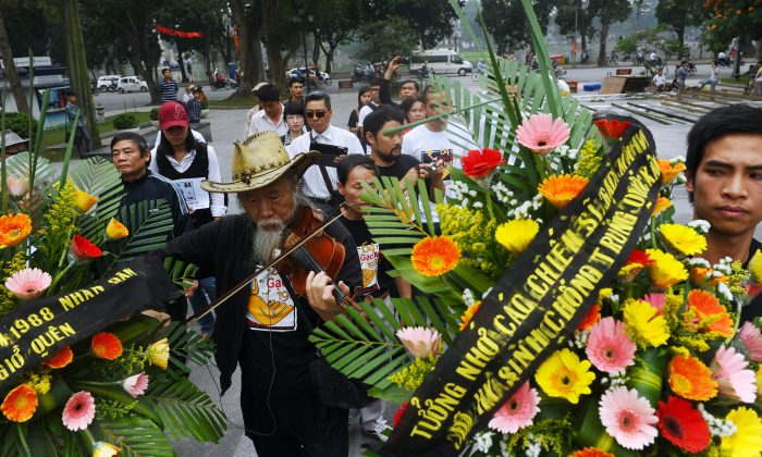 Activists in Hanoi laid flowers and chanted anti-China slogans at a March 14, 2013, protest commemorating the 1988 battle over the contested Spratly Islands in which 64 Vietnamese soldiers died. (Hoang Dinh Nam/AFP/Getty Images)