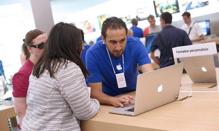 An employee demonstrates Apple's MacBook Pro laptop to a customer in an Apple store in Rosny-sous-Bois, near Paris, France, July 6. (Thomas Samson/AFP/Getty Images)