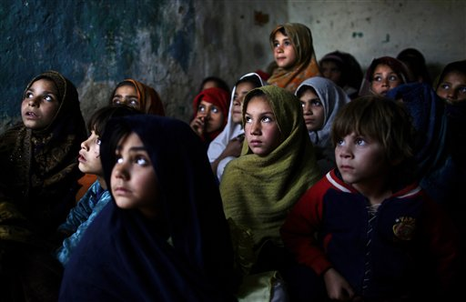 In this Thursday, Jan. 31, 2013, photo, Pakistani schoolgirls, who were displaced with their families from Pakistan's tribal areas due to fighting between militants and the army, listen to their teacher, not seen, while a health worker visiting their school to give  polio vaccines, in a poor neighborhood on the outskirts of Islamabad, Pakistan. Wonder Woman and Supergirl now have a Pakistani counterpart in the pantheon of female superheroes _ one who shows a lot less skin. Meet Burka Avenger: a mild-mannered teacher with secret martial arts skills who uses a flowing black burka to hide her identity as she fights local thugs seeking to shut down the girls' school where she works. (AP Photo/Muhammed Muheisen)