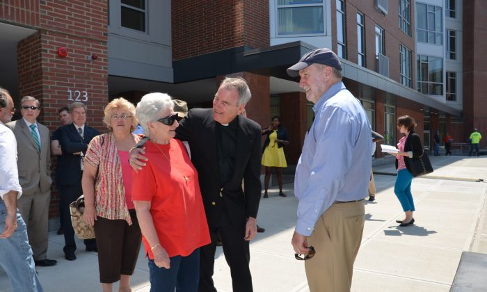 Father Frank Glynn talks with residents at the opening of the Josephine A. Fiorentino Community Center at the Charlesview Residences in Boston, Mass. Creating a community was a central part of development plan for this affordable housing complex. (Deborah Addis, Addis Communications)