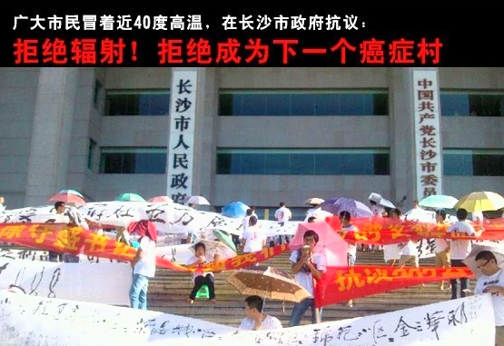 "Protesters against the construction of broadcast transmission towers in Changsha hold banners, while the writing in red above says ""Reject radiation! Reject becoming the next cancer village."" A thousand protesters demonstrated against the project on July 29. (Weibo.com)"