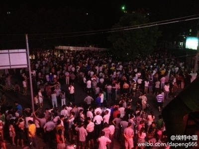 """Local residents gather to prevent the dead body of Deng Zhengjia from being taken away by local authorities. Deng, a watermelon seller, was killed by """"chengguan"""" urban management police in Linwu County, Hunan Province on Wednesday, after an altercation broke out between the two parties. (Weibo.com)"""