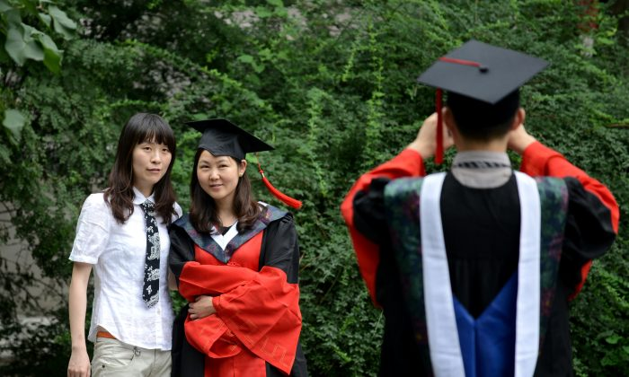 Students pose for photos after a graduation ceremony at a Beijing university on July 11, 2013. Chinese website Shang Daxue recently released a list of 50 bogus universities and colleges that seek to extort tuition money from the students they enroll, especially targeting those who scored low on the national college entrance exam. (Wang Zhao/AFP/Getty Images)