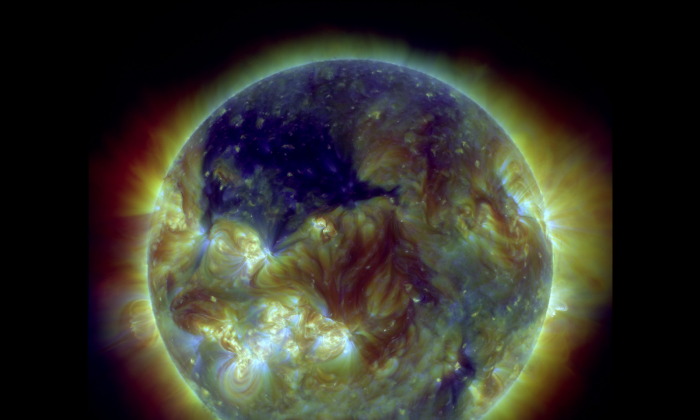 A photo of the sun taken by NASA on July 18, 2013, showing a coronal hole covering much of the upper-left quadrant (pictured in blue). (NASA/SDO)