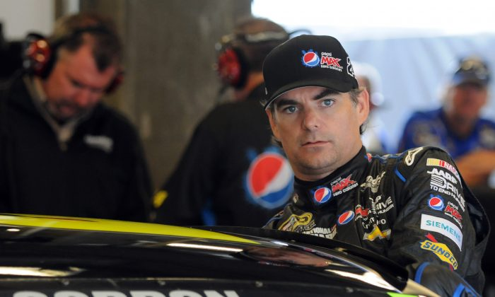 Sprint Cup Series driver Jeff Gordon climbs into his car during practice for the Brickyard 400 auto race at the Indianapolis Motor Speedway in Indianapolis, Saturday, July 27, 2013. (AP Photo/Doug McSchooler)