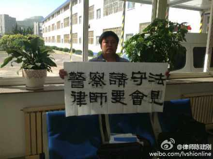 Chinese lawyer Chen Jiangang holds up a banner asking Dalian City police to meet with him and other lawyers defending 13 Dalian Falun Gong practitioners, who were charged for setting up satellite dishes in local residences. On July 5, Chen and 10 other lawyers on the defense team refused to attend the latest court hearing on the case, citing the court's failure to follow proper legal procedures. (Weibo.com)
