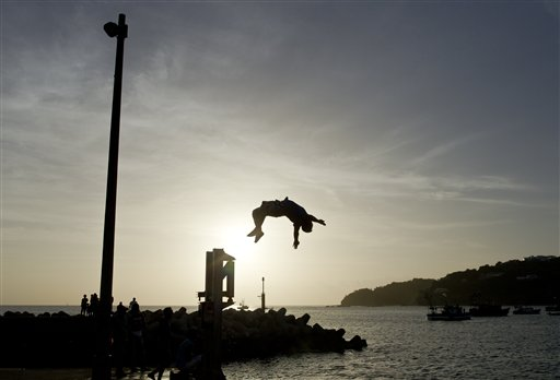 A youth jumps into the Pacific Ocean during a religious procession of the Virgin of Carmen on the shores of San Juan del Sur, Nicaragua, Tuesday, July 16, 2013.  (AP Photo/Esteban Felix)