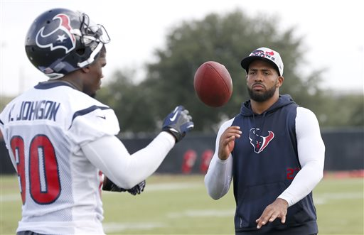 Houston Texans' Arian Foster, right, tosses a football toward Andre Johnson (80) during NFL football training camp Saturday, July 27, 2013, in Houston. The star running back started training camp on the physically unable to perform list with a calf injury received at the beginning of organized training activities. (AP Photo/Pat Sullivan)